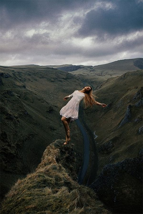 Rosie Hardy leans back precariously at the edge of a hilltop, with a winding river in the background.
