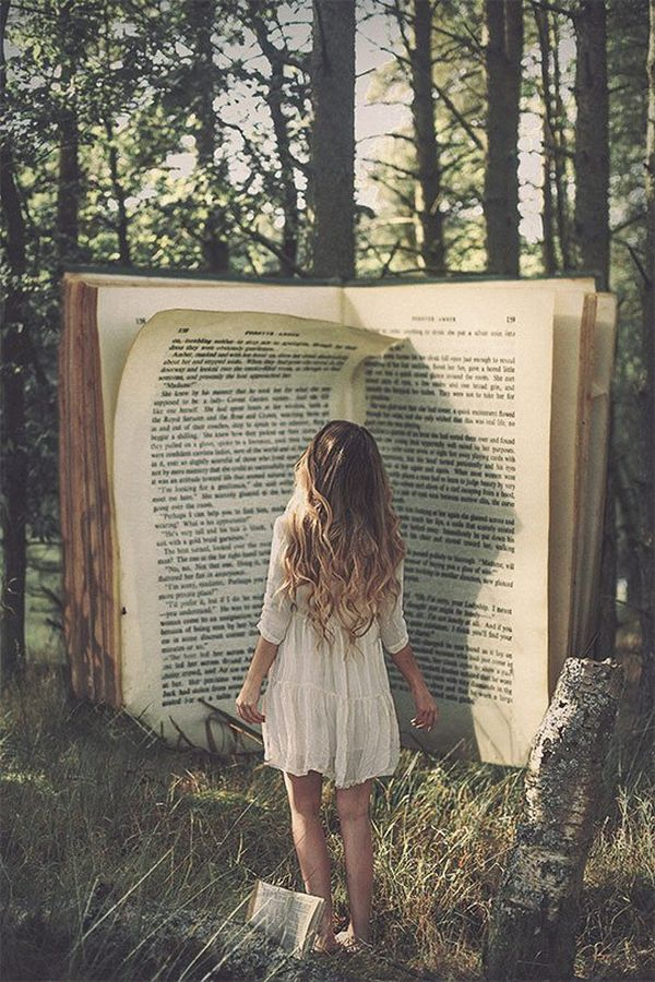 The back of a woman with long hair is seen reading a giant book, in the setting of a wood.
