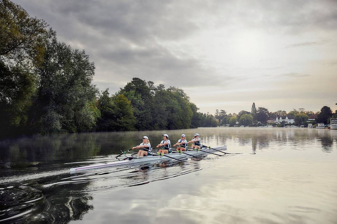 Four women row a narrow boat along a wide river at dawn.