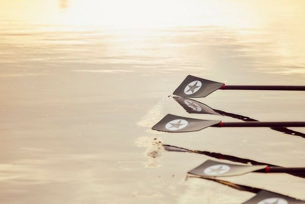 Oar blades are caught mid-stroke, hovering above the water.