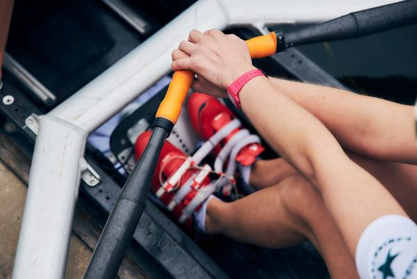 A close-up shows a rower's feet positioning and arms from above.