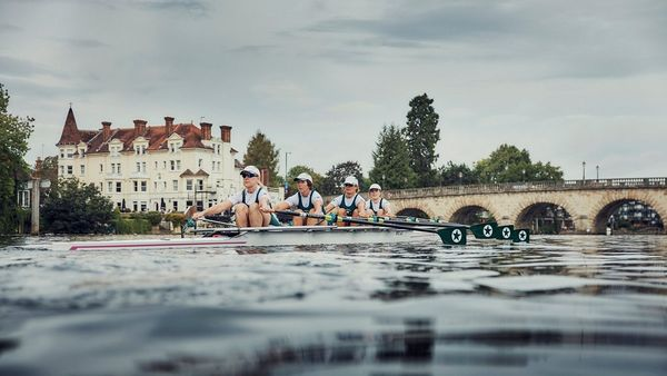 An image taken from the water level showing the rowers in action as they head underneath a bridge.