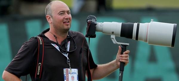 Getty Images sports photographer Warren Little standing in a stadium with his Canon camera and a long lens. © Getty Images