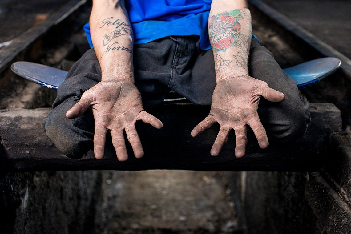 Double leg amputee skateboarder Felipe Nunes sits on a skateboard in a train garage while showing his hands, covered in dirt from being used to propel himself along during a skateboarding session.