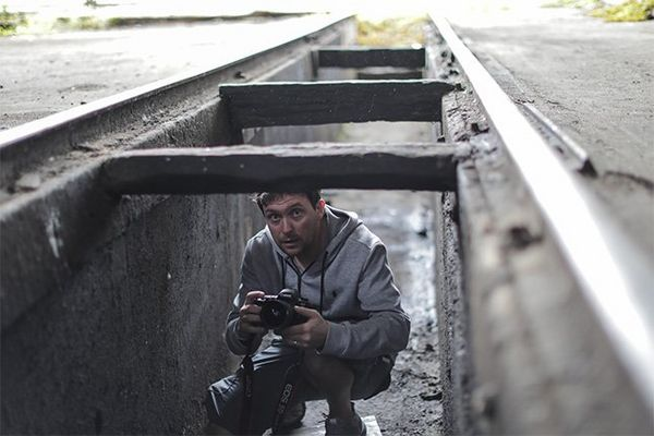Photographer Samo Vidic crouches in the cavity underneath a train garage rail rack, holding his Canon EOS 5D Mark IV.