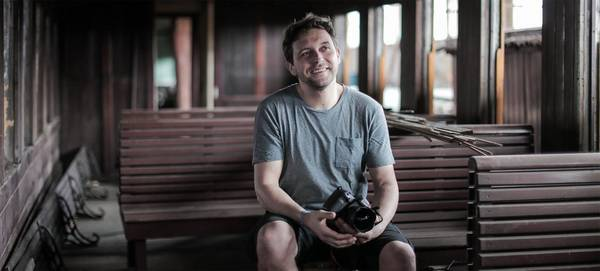 Photographer Samo Vidic is pictured in a train carriage, holding his Canon EOS 5D Mark IV.