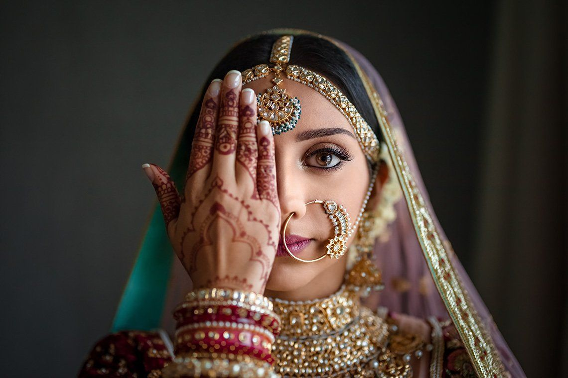 An Indian woman in silk wedding clothes and opulent gold jewellery holds a henna tattooed hand in front of one eye.