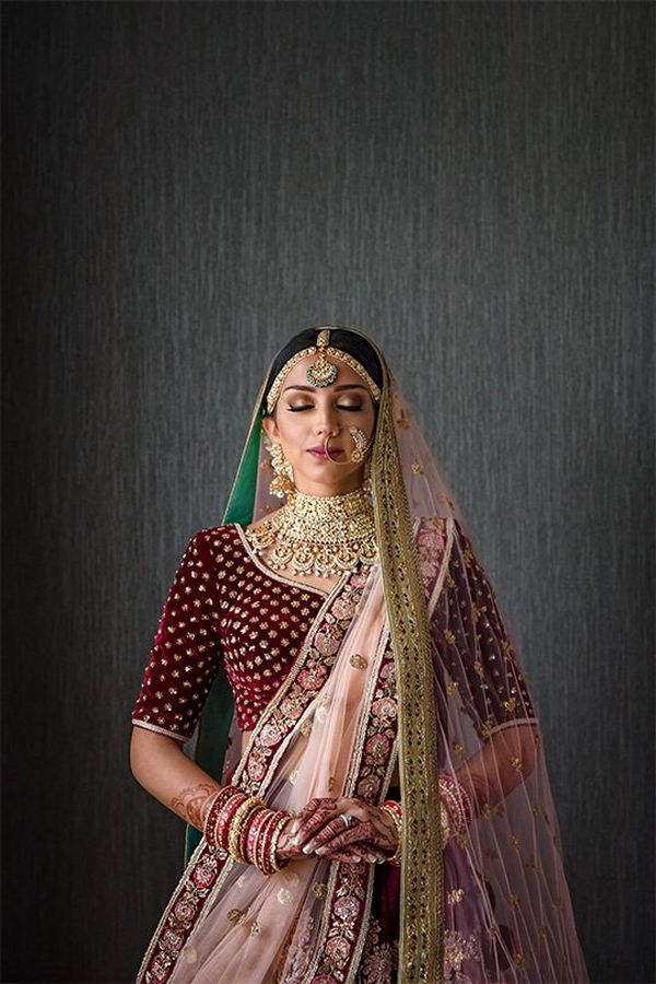 An Indian woman in a deep red wedding sari embroidered with gold, plus gold jewellery and henna patterns on her hands, stands peacefully in front of a dark grey wall.