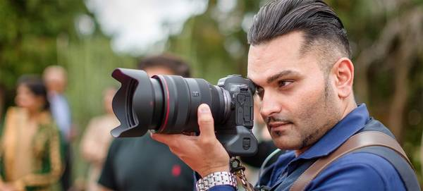 Wedding photographer Sanjay Jogia crouches low among some stones, holding his Canon camera to his eye.