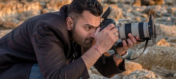 Wedding photographer Sanjay Jogia crouches down low on a beach, holding his Canon camera and long lens to his eye to photograph someone out of shot.