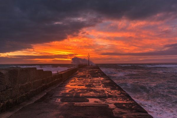 Sunset over the sea wall at Porthleven, Cornwall, streaking the sky with red and gold. Photo by Carla Regler.