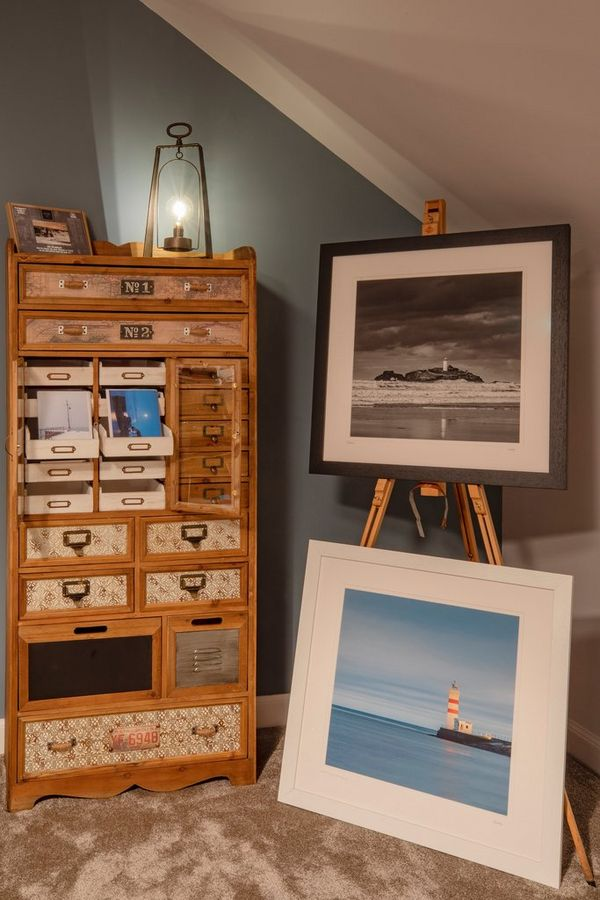 Photo prints displayed on an easel next to an ornate wooden chest of drawers, with smaller prints in some of the drawers.