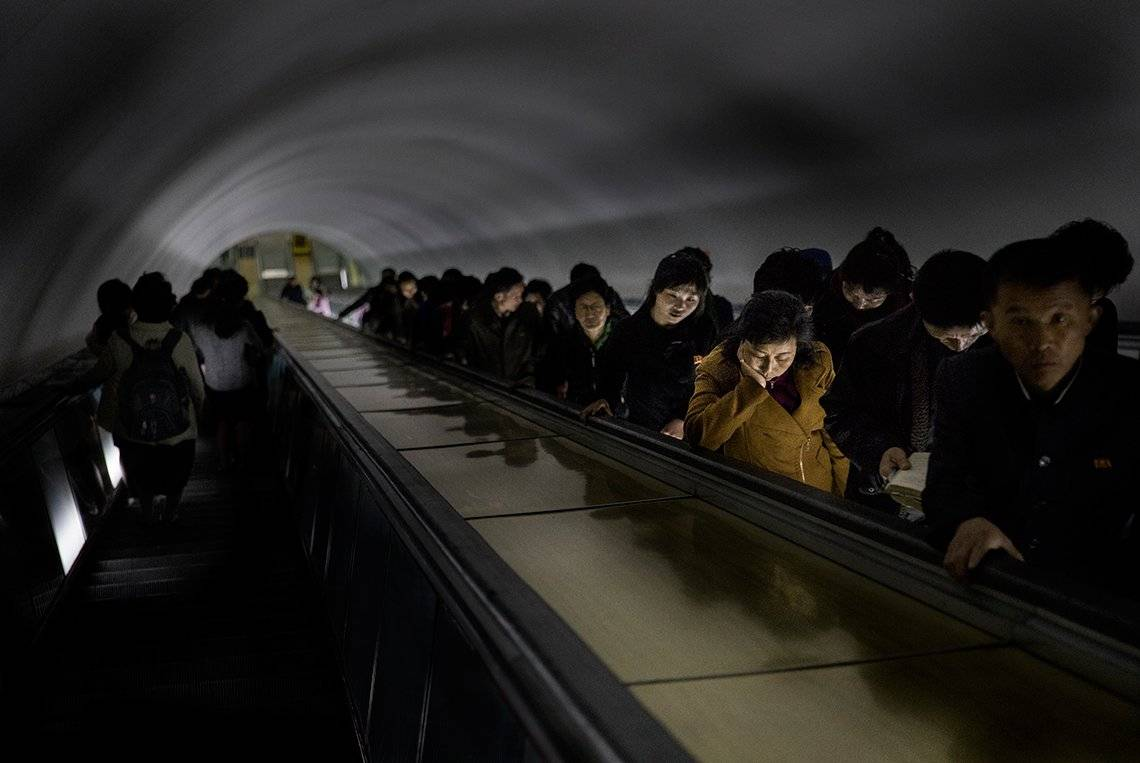 North Korean people travel up a tall metro escalator at rush hour. Photo by Roger Turesson on a Canon EOS 5D Mark IV.