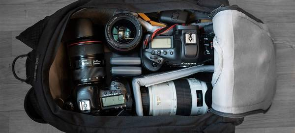 A camera bag is open, revealing two Canon DSLRs, lenses and accessories.