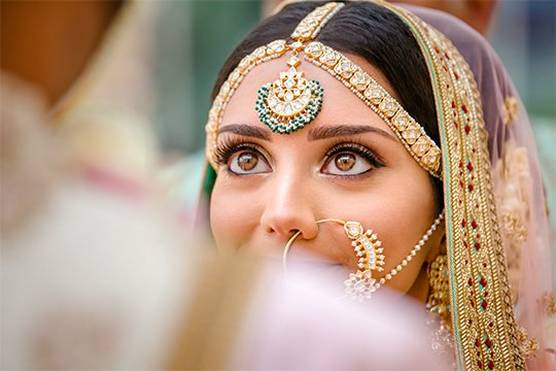 An Indian bride, photographed over her groom's shoulder, looking up at him.