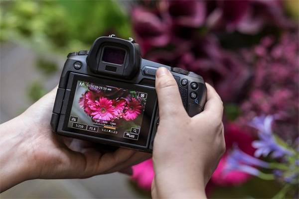 Photographer Guia Besana attaches a lens to the Canon EOS R.