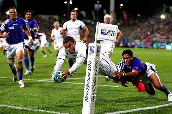 South Africa rugby player Bryan Habana dives to score a try, a Samoa rugby player grabbing his leg Photo by Hannah Peters.