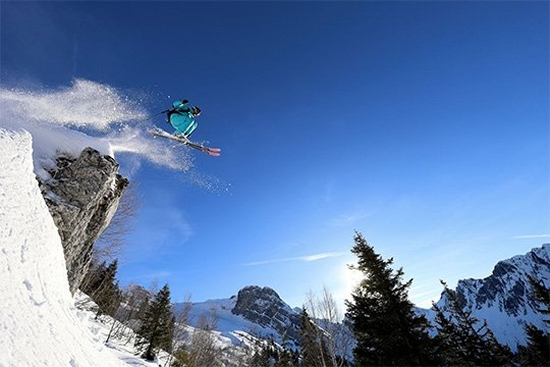 A skier flies into the air off the edge of a mountain. Photo by Martin Bissig.