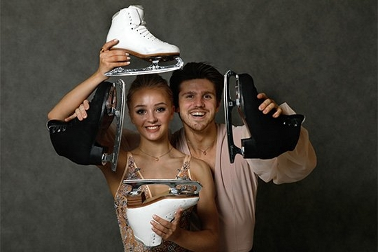 A male and female ice skater holding their ice skating boots. Photograph by Andrey Golovanov.