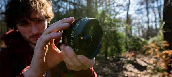 Filmmaker Freek Wonderland holds up a Canon CN-E14mm T3.1 FP X Sumire Prime lens.