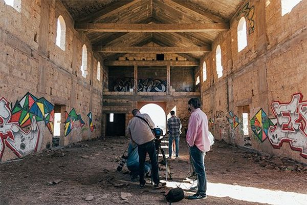Hans von Sonntag and film crew at work inside a deserted chapel, with glaring light streaming in through the open windows and doorways.