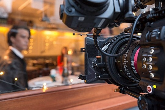 Filming the warmly-lit interior of a café through the window with a Canon EOS C700 FF camera and Sumire Prime cine lens.