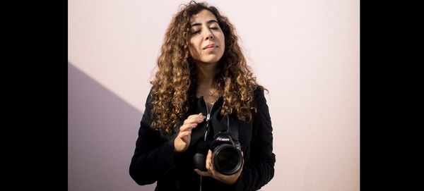 Photographer Tasneem Alsultan holds a Canon DSLR camera and lens in front of a pink wall.