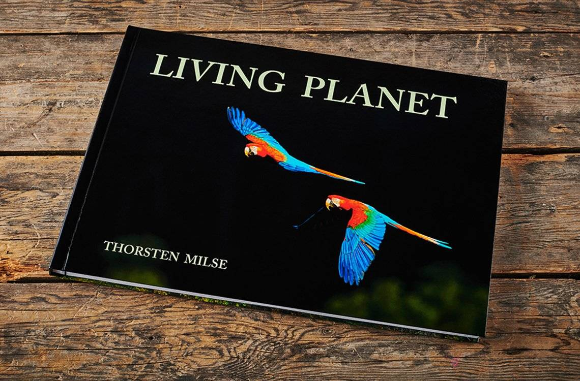 Thorsten Milse's Living Planet hdbook, with red macaws in flight on the front cover.
