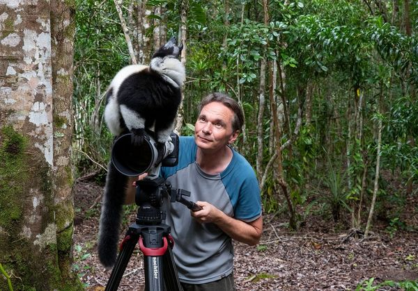 Wildlife photographer Thorsten Milse standing behind a camera on a tripod, looking at the animal that is sat on the camera's lens.
