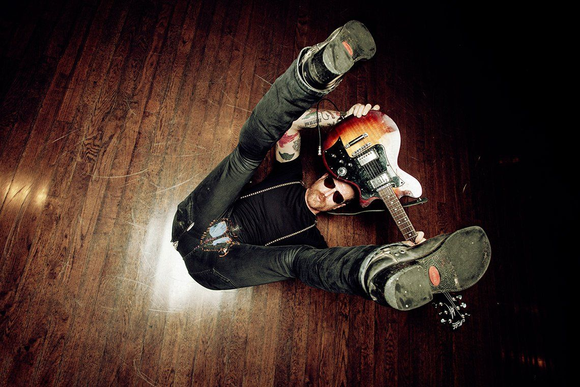 Guitarist Jesse Hughes lying on his back on a wooden floor, legs raised, holding a guitar above his head with both hands