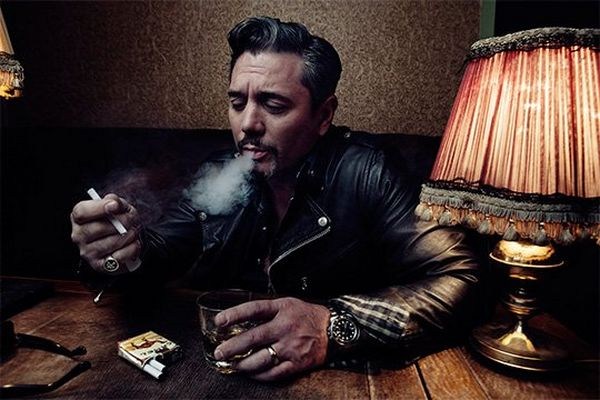 Huey Morgan, wearing a black leather jacket, sits at a wooden table, blowing smoke from a cigarette