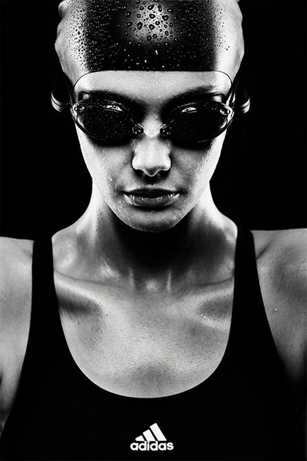 A high-contrast mono image of the head and shoulders of a female swimmer wearing goggles and a cap
