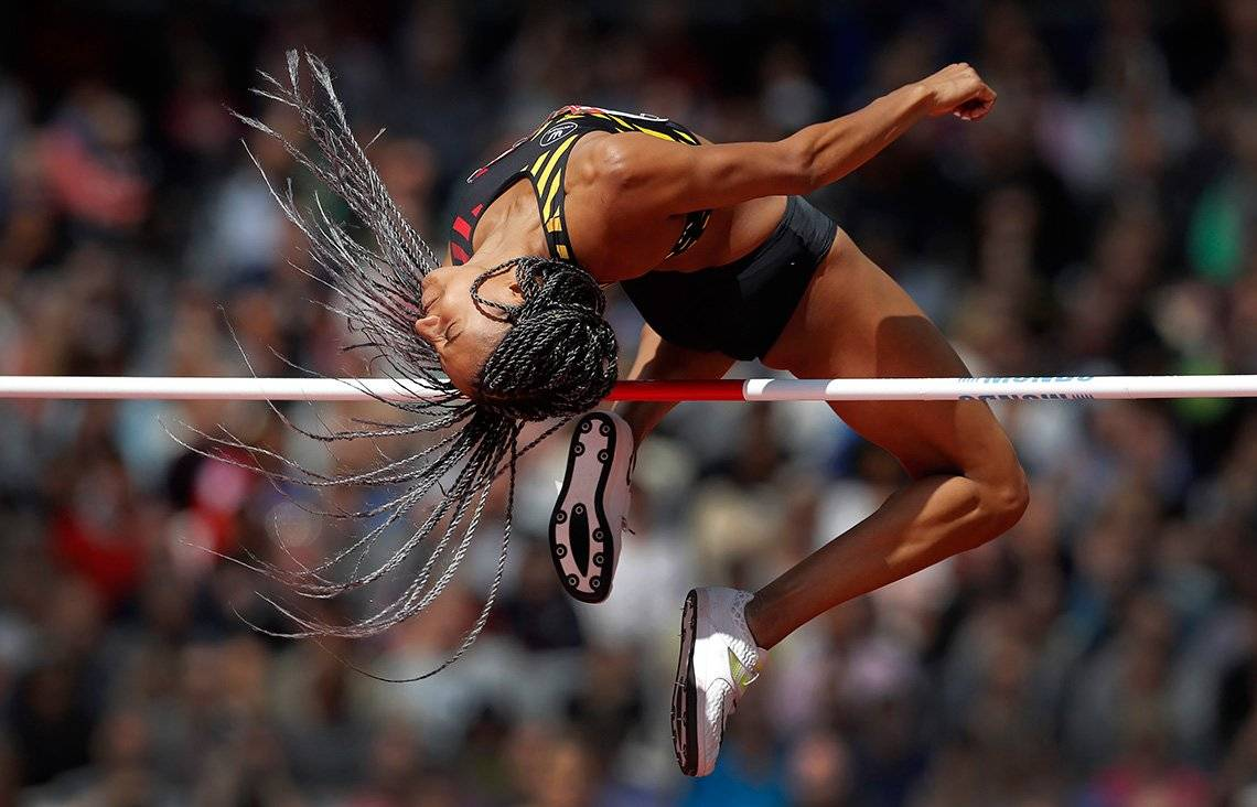 A female athlete soars over the high jump, her braided hair swirling around her head.