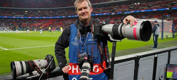 Photographer Tom Jenkins stands by the side of a football pitch with three Canon cameras fitted with telephoto lenses.