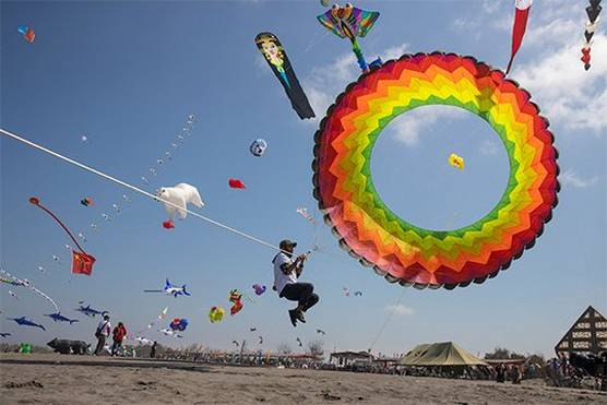 A kite-handler is lifted off the ground by his circular, rainbow-coloured kite. Photo by Ulla Lohmann.