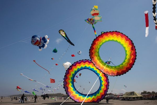 Colourful kites of different shapes fill the sky.