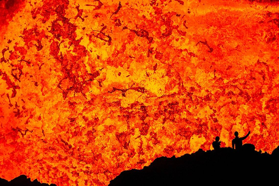 Two scientists silhouetted against the lava lake inside the Benbow crater on the volcanic island of Ambrym.
