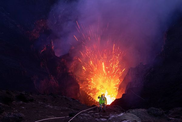 A geologist abseiling into an active volcano.