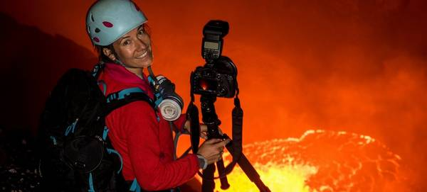 Canon Ambassador Ulla Lohmann standing at the edge of a lava-filled crater, holding a Canon camera attached to a tripod.