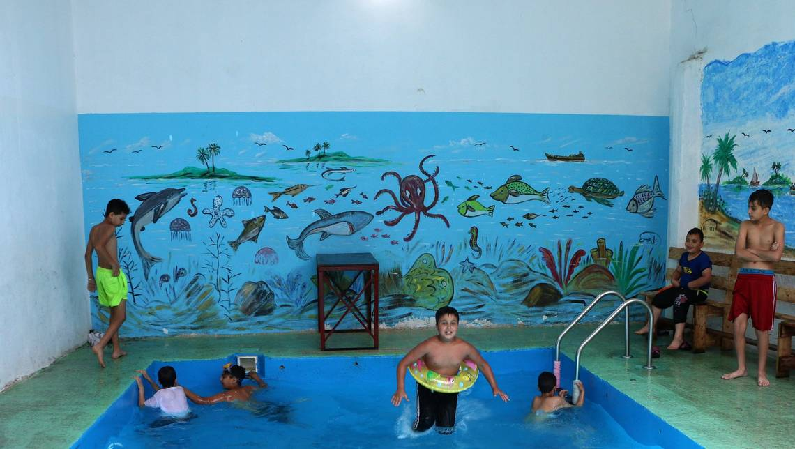 Children play in a swimming pool in a refugee camp in Lebanon, captured by a refugee living in the camp.