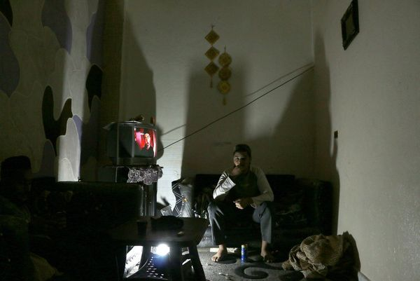 A project participant's image, showing a man sitting in semi-darkness watching television, to illustrate the boredom experienced within the camp.