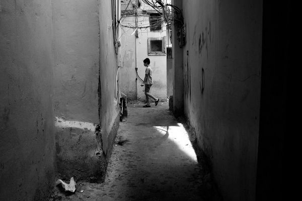 A child playing in an alleyway during summer where it can be dangerous with low-hanging electrical wires. Photographed by a refugee living in the camp in Lebanon.