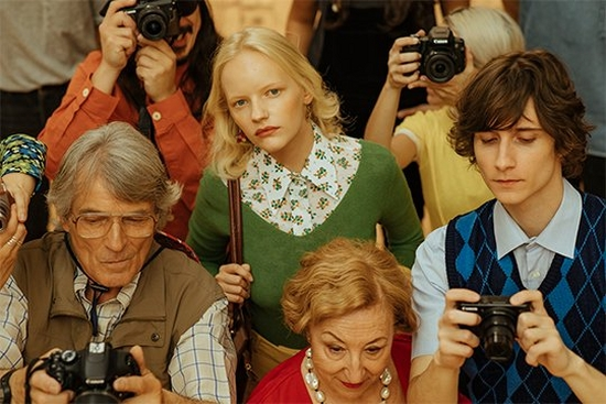 A woman in 1970's-style clothes looks up from a crowd in a shot from Javier Cortés's fashion film, Beauty is Subjective.