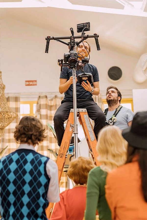 Javier Cortés sits on a high ladder with his Canon EOS 5D Mark IV rigged to shoot video.