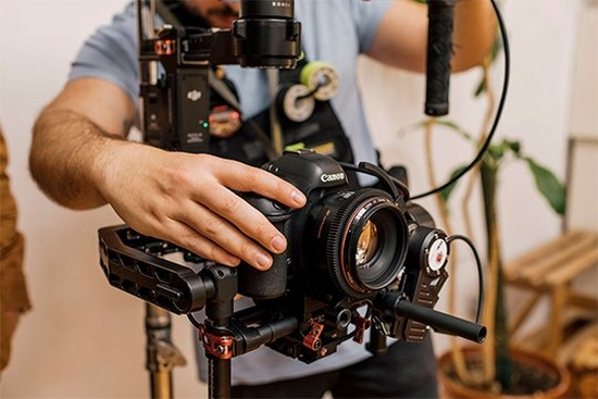 A videographer makes adjustments to a Canon EOS 5D Mark IV on a film set.