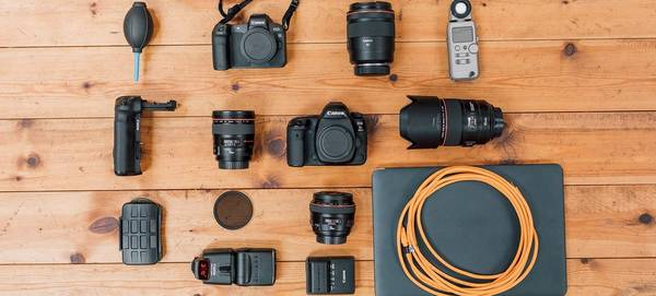 Javier Cortés's Canon photography kit is laid out on a wooden table top.