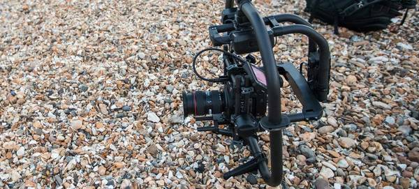 A Canon EOS C200 camera fitted in a gimbal sat on pebbles.