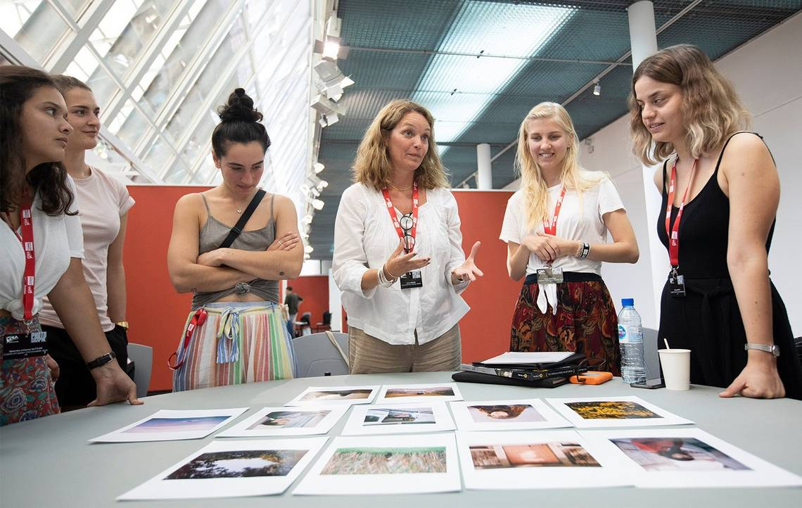 A group of students and a mentor at Visa pour l'Image discuss the images on the table in front of them.