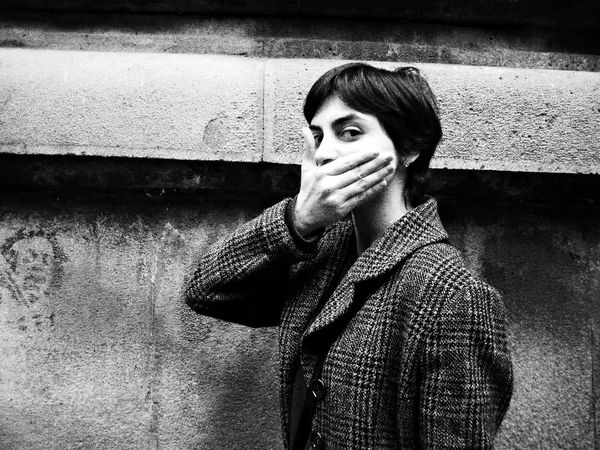 A black-and-white shot of a young woman with a wearing a tweed jacket, covering her mouth with her hand.