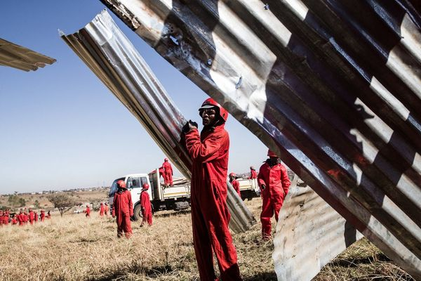 Construction workers wearing red boiler suits hold up sheets of corrugated metal in a field.